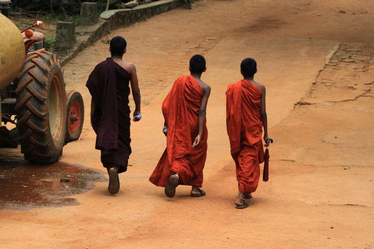 Rear View Of Monks Walking On Road