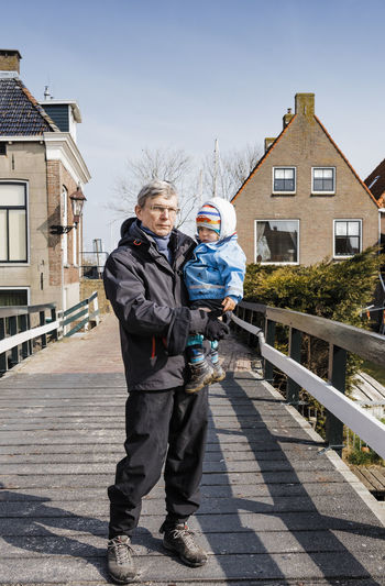 Portrait Of Grandfather Carrying Baby Girl While Standing On Footbridge Against Houses