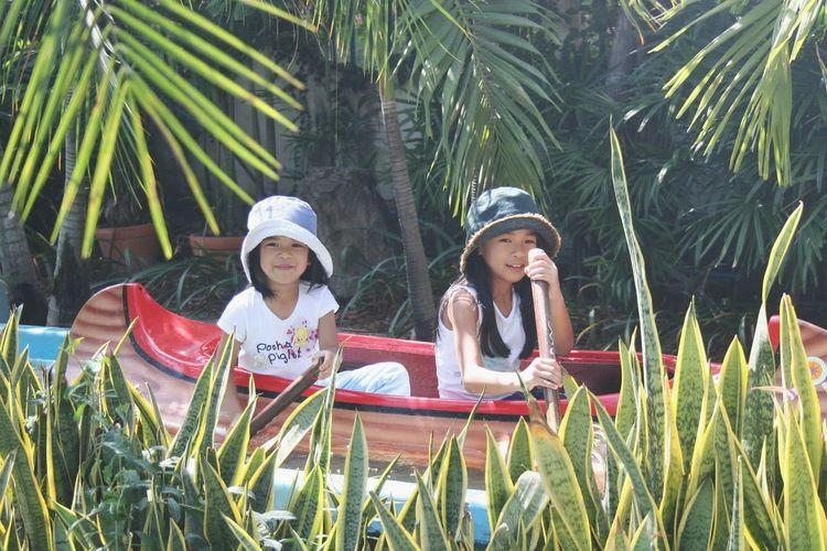 Portrait of girls sitting in kayak amidst grass