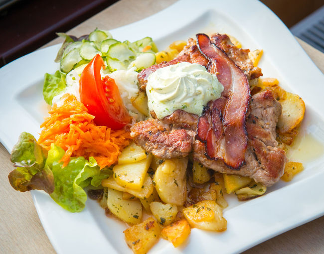 Traditional Bavarian pork steak with potato. Food Food And Drink Freshness Plate Ready-to-eat Healthy Eating Meat Vegetable Close-up Still Life Table Meal Indoors  Serving Size Wellbeing High Angle View No People Salad Potato Indulgence