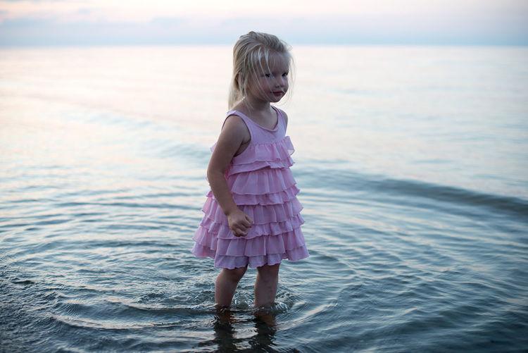 Girl standing in sea against sky