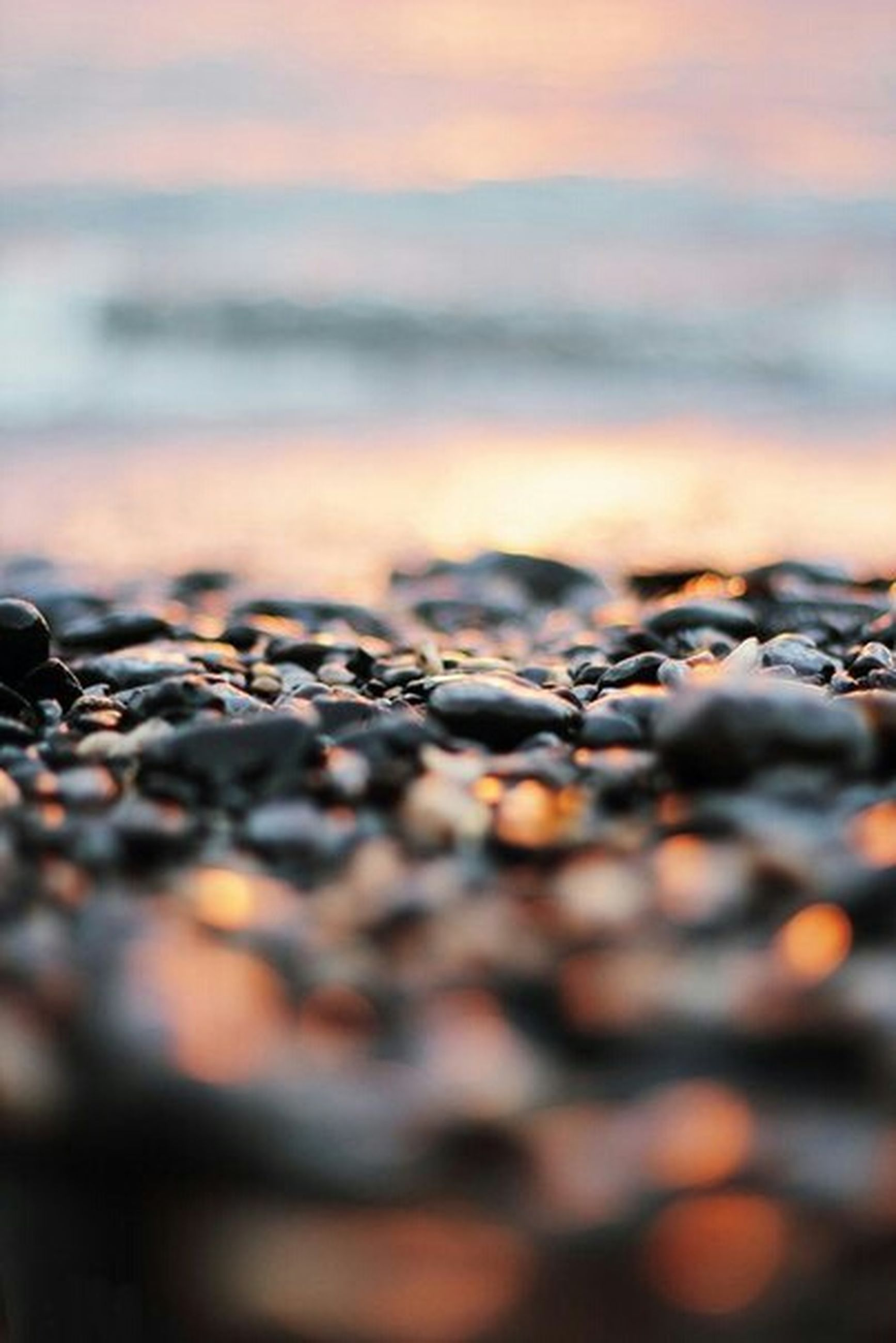 selective focus, sunset, sky, surface level, focus on foreground, close-up, nature, tranquility, beauty in nature, beach, scenics, cloud - sky, tranquil scene, outdoors, stone - object, pebble, no people, abundance, idyllic, orange color
