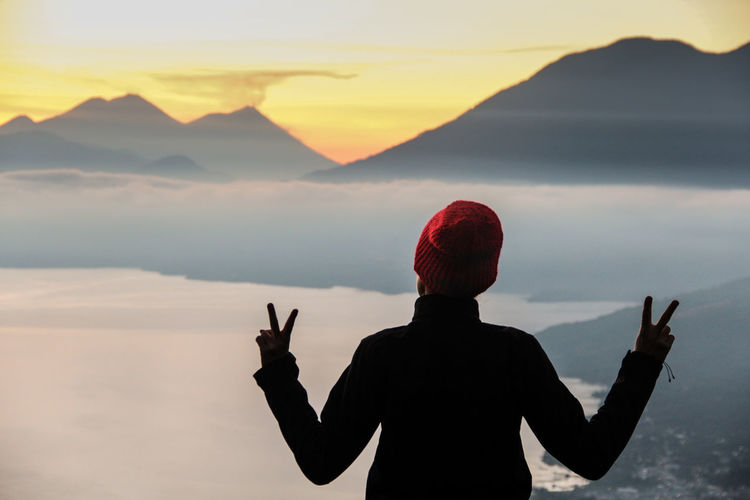 Woman standing on mountain in foggy weather against sky during sunset