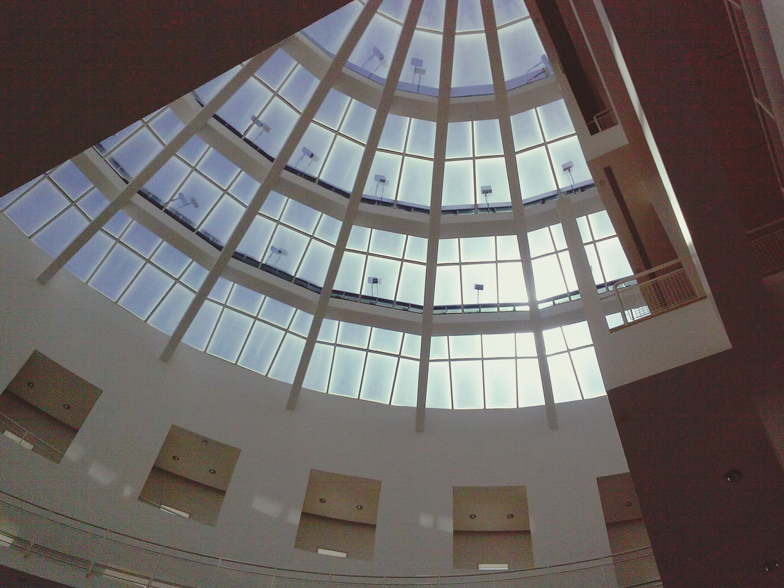indoors, architecture, built structure, ceiling, low angle view, glass - material, architectural feature, pattern, window, skylight, modern, design, transparent, interior, building exterior, famous place, building, no people, geometric shape, directly below