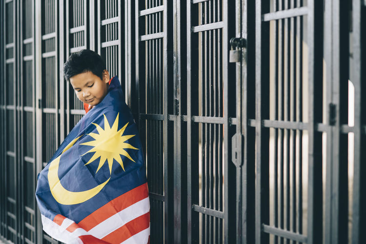 Side view of boy wearing malaysian flag by fence