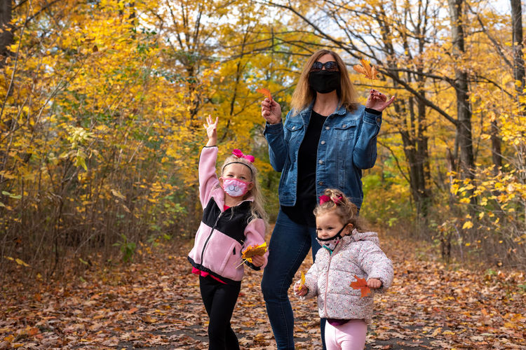 Mother with daughters wearing mask standing in forest during autumn