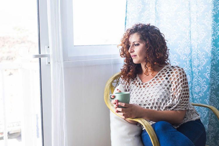 Woman Holding Coffee Cup While Sitting At Home