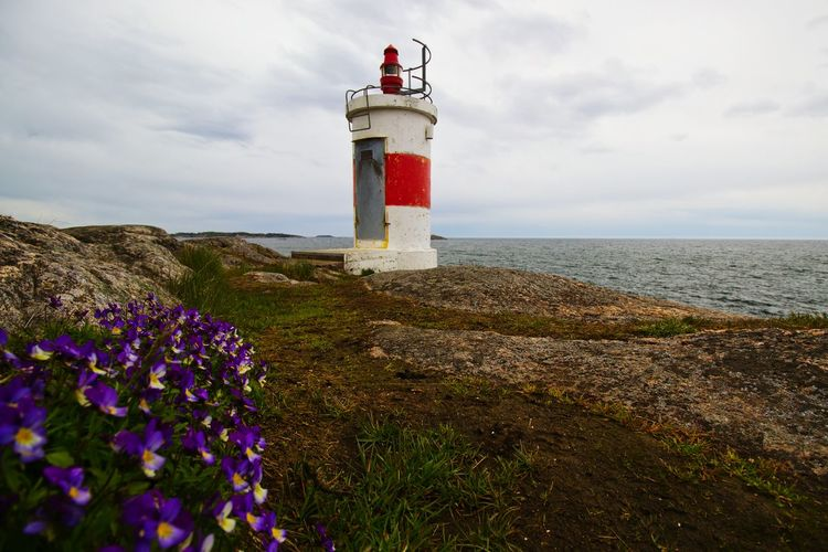 Lighthouse on cliff against sky