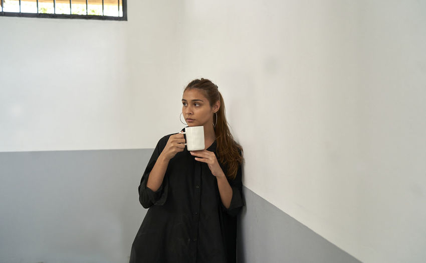 Young woman drinking coffee cup against wall