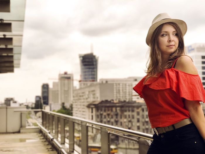 Beautiful Woman Standing By Railing At Building Terrace Against Skyscrapers In City