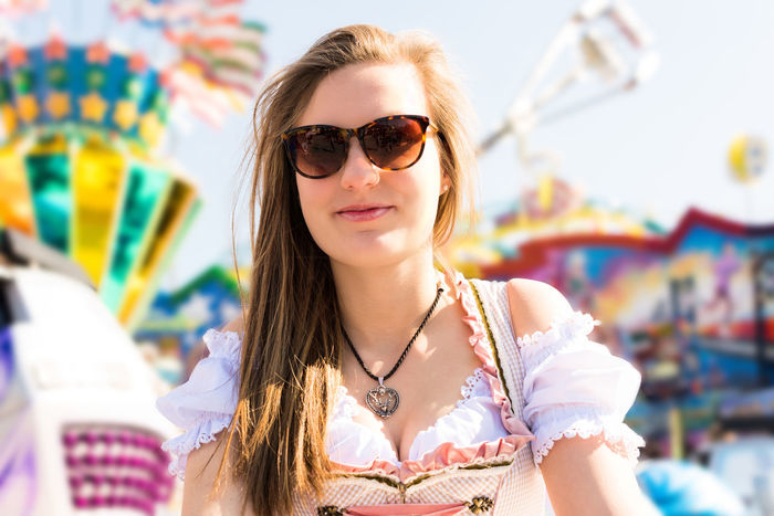 Attractive young woman at German funfair Oktoberfest with traditional dirndl dress and joyride in the background Attractive Female Bavaria Fun Funfair Lederhosen Munich Oktoberfest Portrait Of A Woman Woman Attractive Dirndl Funfair Ride Girl Merry Go Round Portrait Tracht Traditional Young Adult Young Woman Young Woman Smiling