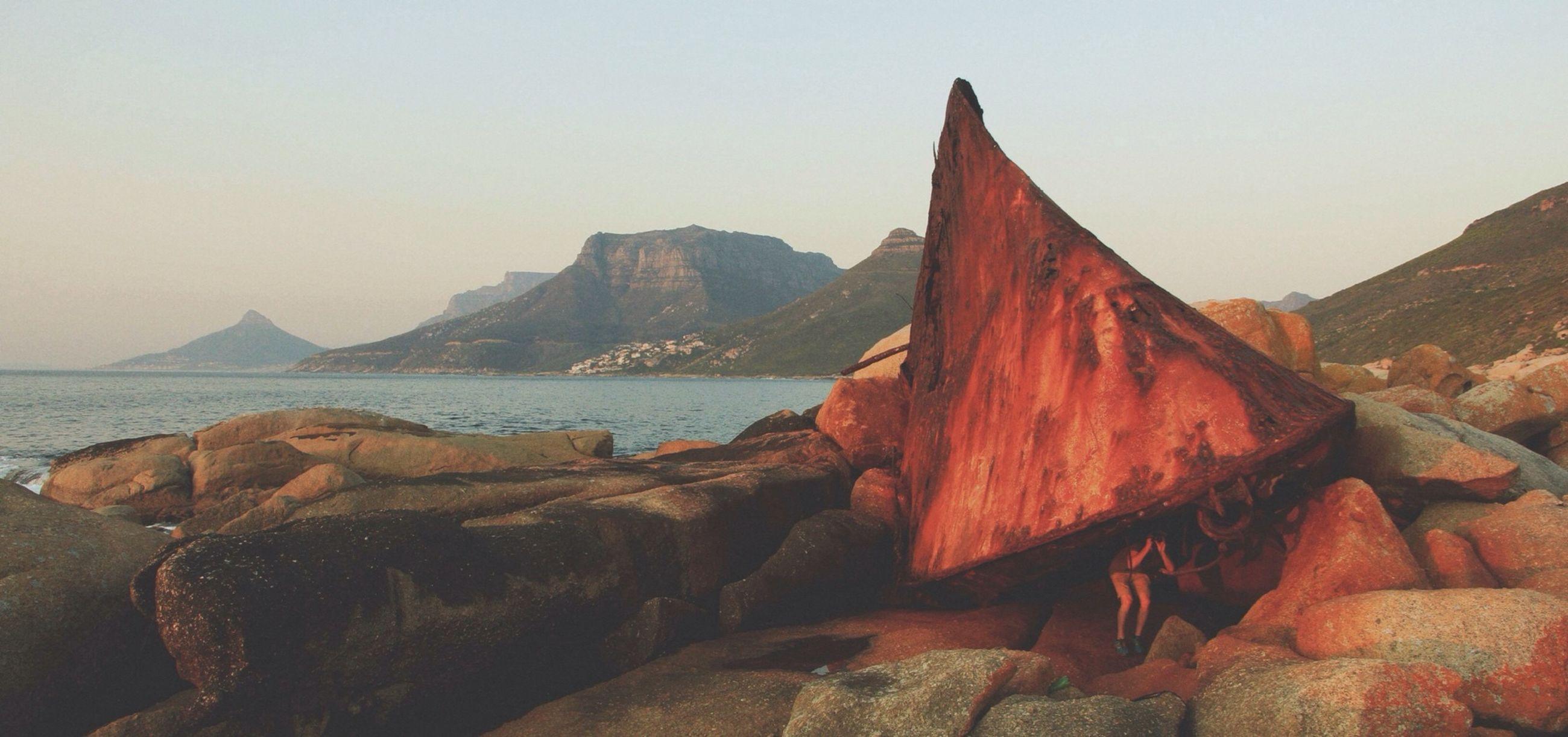 mountain, water, clear sky, tranquility, tranquil scene, scenics, sea, beauty in nature, rock - object, nature, rock formation, copy space, sky, mountain range, transportation, idyllic, beach, non-urban scene, outdoors, sunlight