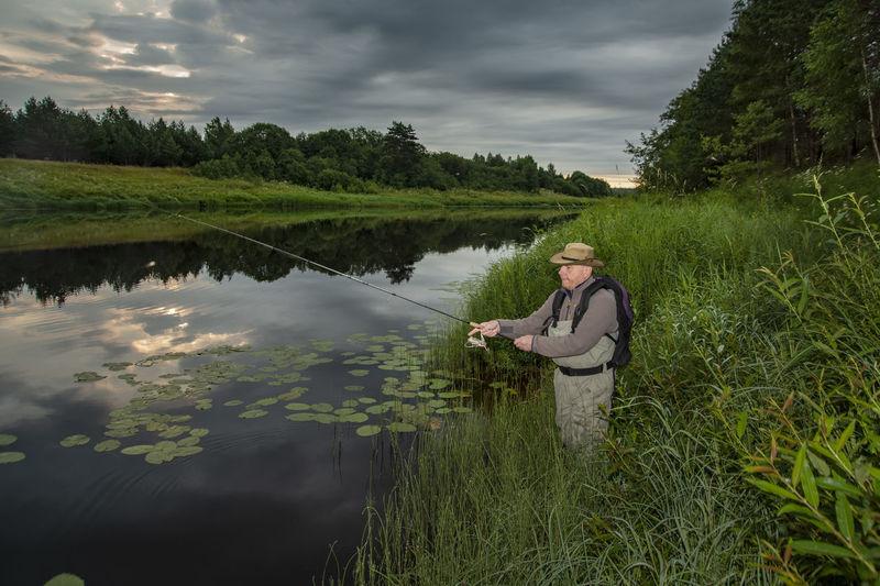 Mature man fishing at lake against sky