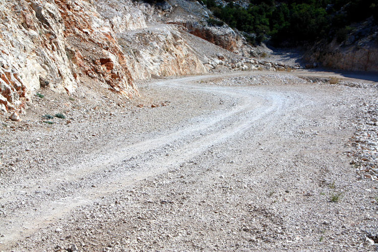 Macadam road curving trough rocky mountain Beauty In Nature Day Direction Dirt Dirt Road Environment High Angle View Land Macadam Nature No People Non-urban Scene Outdoors Road Rock Rock - Object Rock Formation Solid The Way Forward Tranquility Transportation