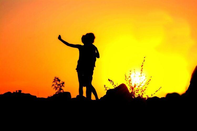 Silhouette people on rocks against orange sunset sky