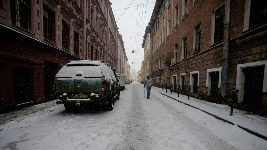 Transportation Mode Of Transportation Snow Cold Temperature Winter Architecture Street Building Exterior City Land Vehicle Snowing Built Structure Motor Vehicle City Street Car on the move Day Nature Building No People Blizzard Outdoors Extreme Weather Alley Russia