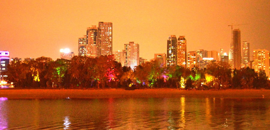 Architecture Beauty In Nature Building Exterior Built Structure City Cityscape Growth Illuminated Lake Modern Nature Night No People Orange Color Outdoors Reflection Scenics Sharjah Uae Sky Skyscraper Sunset Tree Urban Skyline Water Waterfront