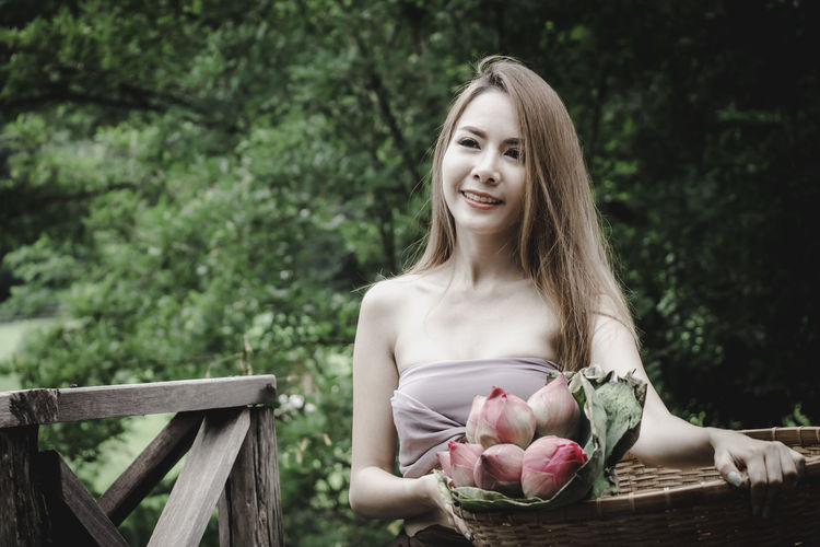 She collected the lotus to pay homage. Beautiful Woman Beauty Day Food And Drink Freshness Front View Hairstyle Leisure Activity Lifestyles One Person Plant Portrait Real People Smiling Tree Women Wood - Material Young Adult Young Women