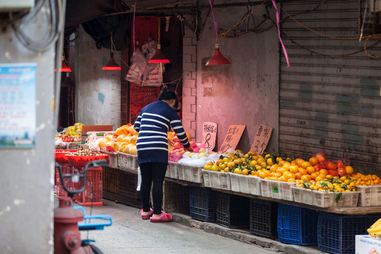 Full length rear view of man standing at market stall