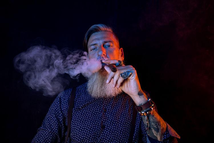 Portrait Of Man Smoking Cigar Against Black Background