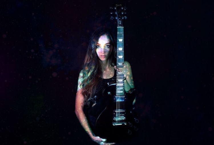 Portrait of woman holding guitar in darkroom