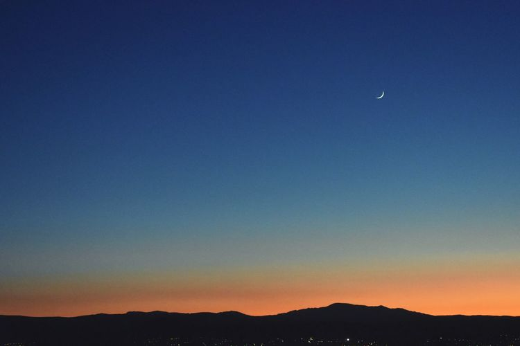 Scenic view of silhouette mountains against clear sky at night