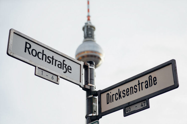 Low angle view of road sign against sky berlin