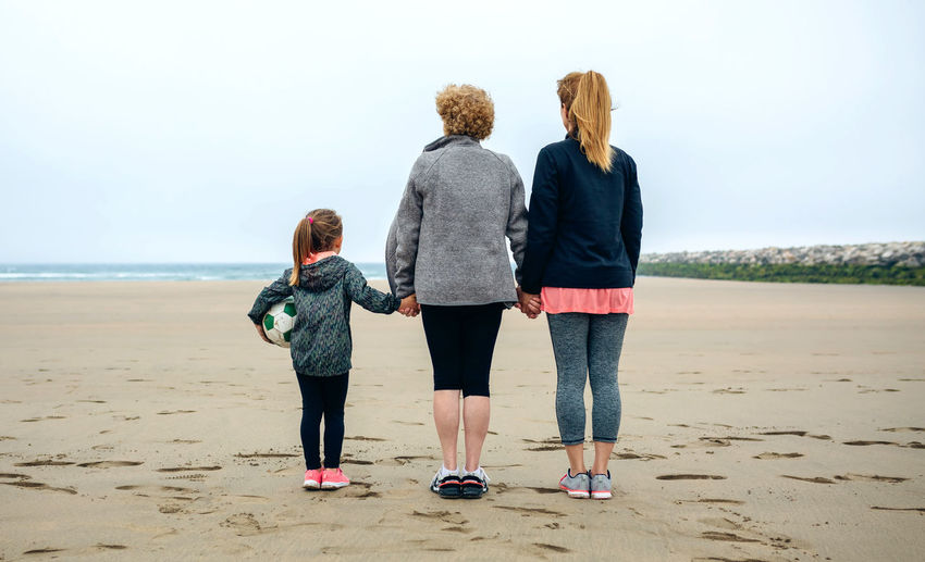 Rear View Of Family Standing At Beach