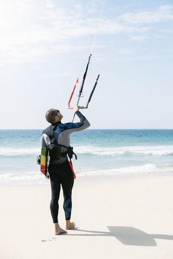 Full length of man holding umbrella on beach