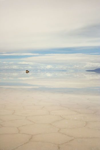 Vehicle With Reflection Of Clouds At Salar De Uyuni