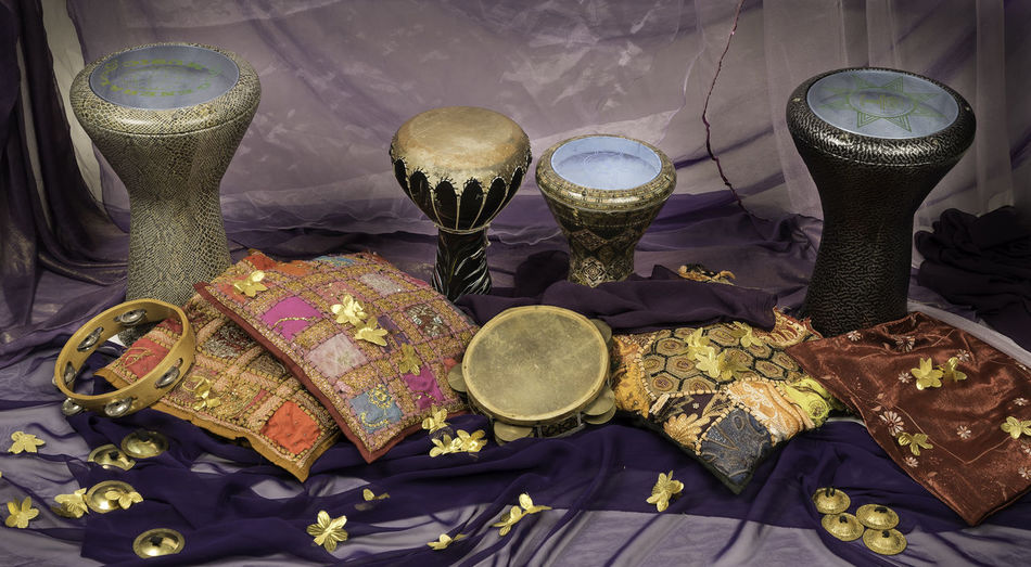 Musical instruments of a bellydance percussiongroup with darbuka's, tambourines and zills Zills Tomtom Togetherness Tambourine Purple Percussion Instrument Percussion No People Musical Instrument Making Music Gold Purple Indoors  High Angle View Flower Drums Doumback Drum Day Darbuka Cymbal Cushion Close-up Celebration Bellydance Belly Dance Arabic Music