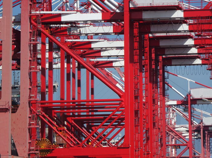 A row of large container cranes at Kaohsiung Port Container Port Gantry Cranes Logistics Trolley Beams Cargo Container Container Terminal Equipment Freight Transportation Girders Machinery Metal Pulley Red Shipping