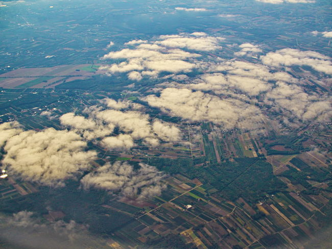 Aerial patchwork landscape view under the clouds Aerial View Cloud - Sky Environment Scenics - Nature Landscape Beauty In Nature Nature Patchwork Landscape Land Agriculture No People Day Tranquil Scene Rural Scene Sky Field Outdoors Tranquility Airplane Cloudscape View Into Land Above