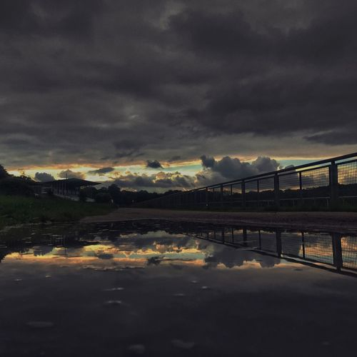 Bridge over river against cloudy sky during sunset