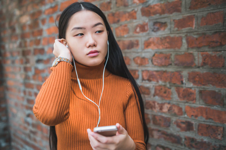 Woman listening music over mobile phone against brick wall