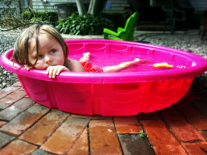 Close-up of a cute girl in pink water tub