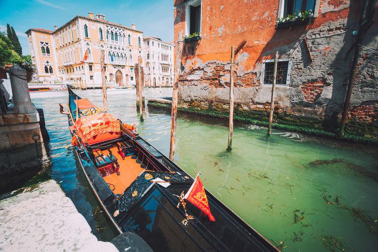 Gondola moored in canal against buildings