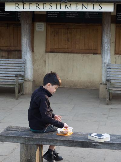 Full length of boy having food on seat