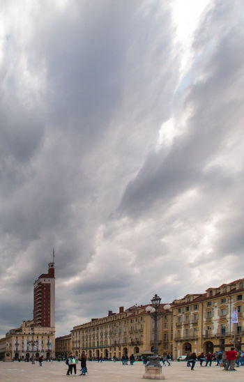 People in city against cloudy sky