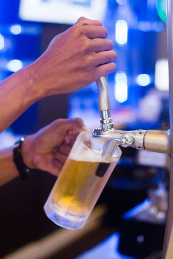 Close-up of cropped hands pouring beer in glass from tap