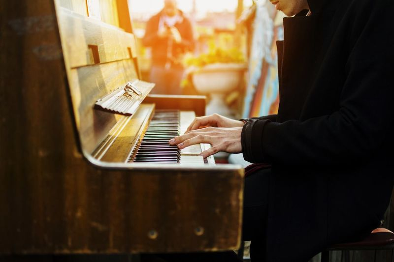 Midsection of man playing piano outdoors
