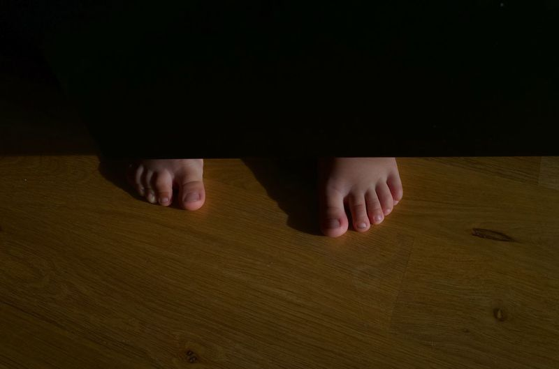 Low section of child on wooden table