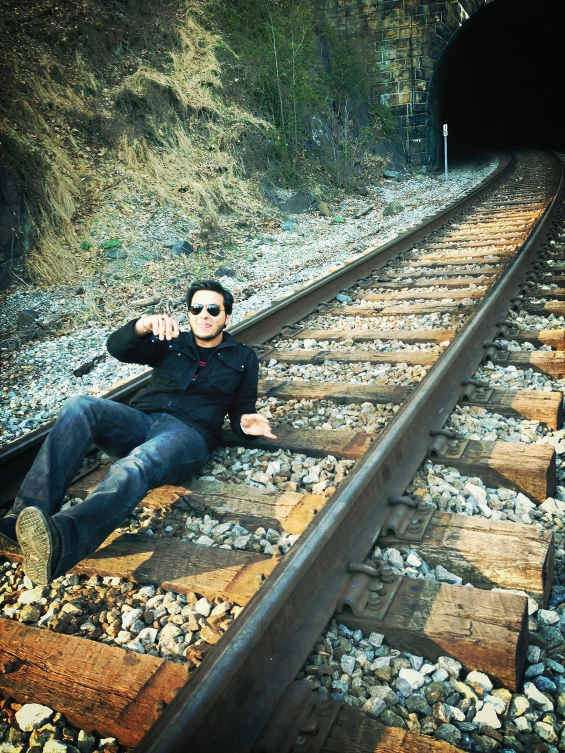 lifestyles, leisure activity, young adult, casual clothing, standing, portrait, person, full length, railroad track, looking at camera, young men, front view, rock - object, sitting, built structure, smiling, technology