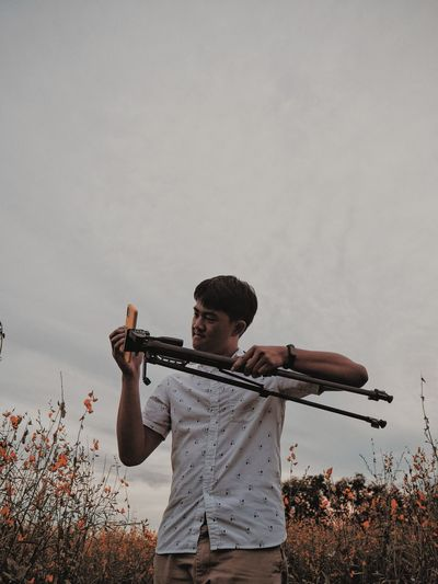 Young man holding tripod against sky