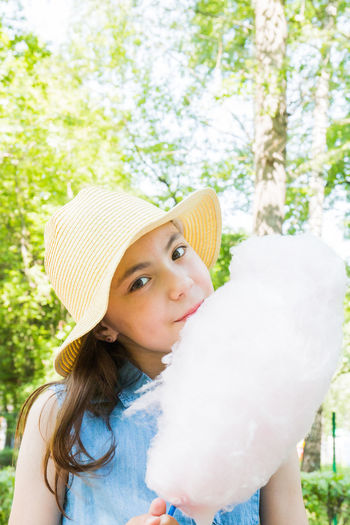 portrait of cute girl in hat eating cotton candy in park in summertime. summer vacation. Beach Summer Travel Vacation Holiday Background Tropical Relax Blue Nature Outdoor Resort Concept Tourism Lifestyle Child Family Happy Kid Water Leisure Relaxation Sand Sky Girl Woman Board Vintage Seashell Playing Desert Healthy Swimsuit Sunbathing Active Preschool Cartoon Colorful Shell Float Wooden Under Scenic Fun Children Activity Park Summertime Candy Sweet