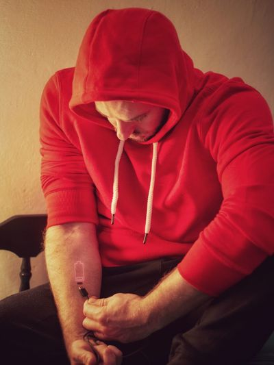 Midsection of man holding red while sitting against wall