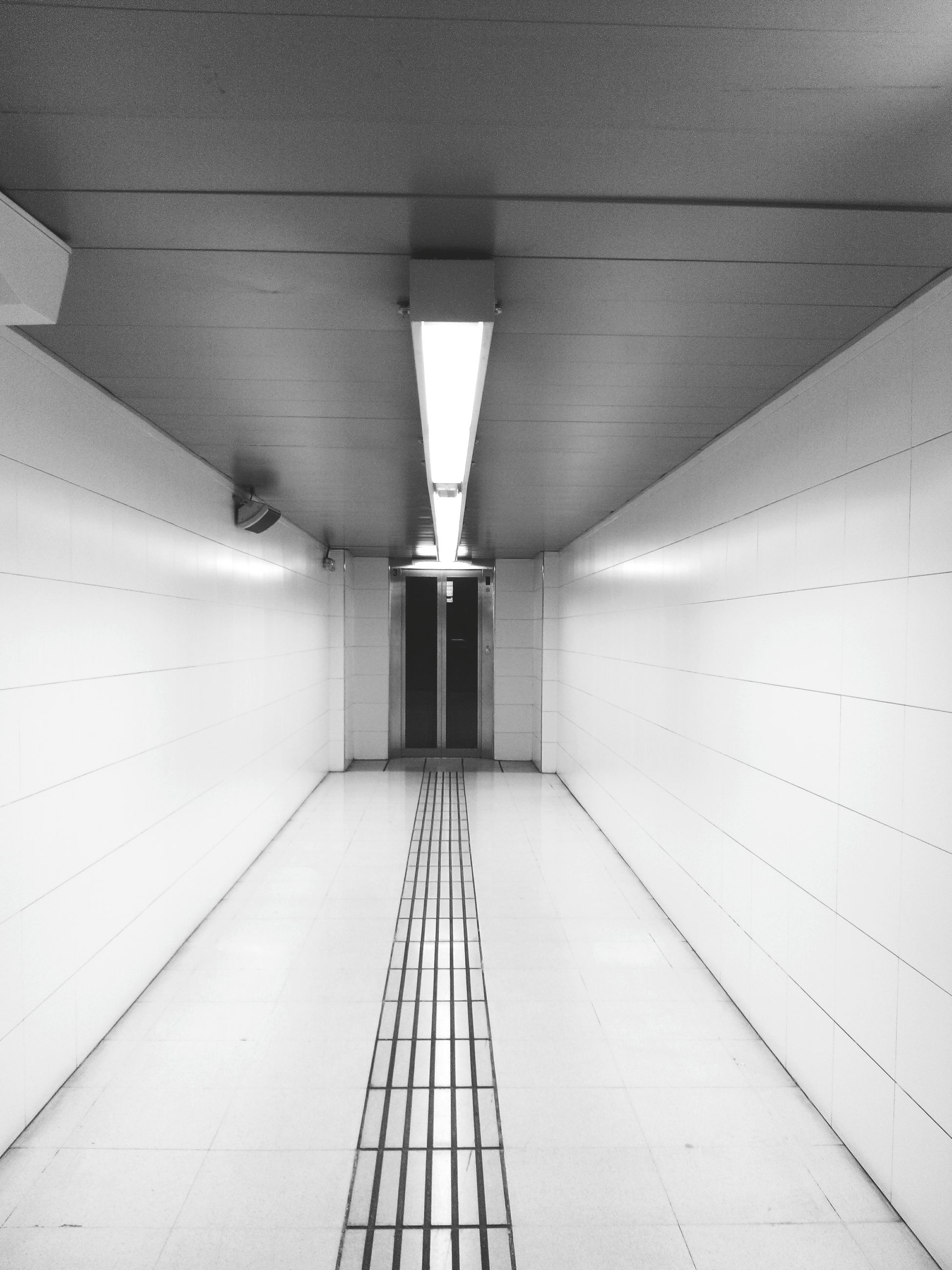 indoors, ceiling, architecture, built structure, the way forward, illuminated, diminishing perspective, corridor, lighting equipment, empty, building, vanishing point, modern, flooring, tiled floor, wall - building feature, interior, architectural feature, low angle view, no people