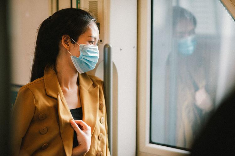 Businesswoman wearing mask looking through window in train