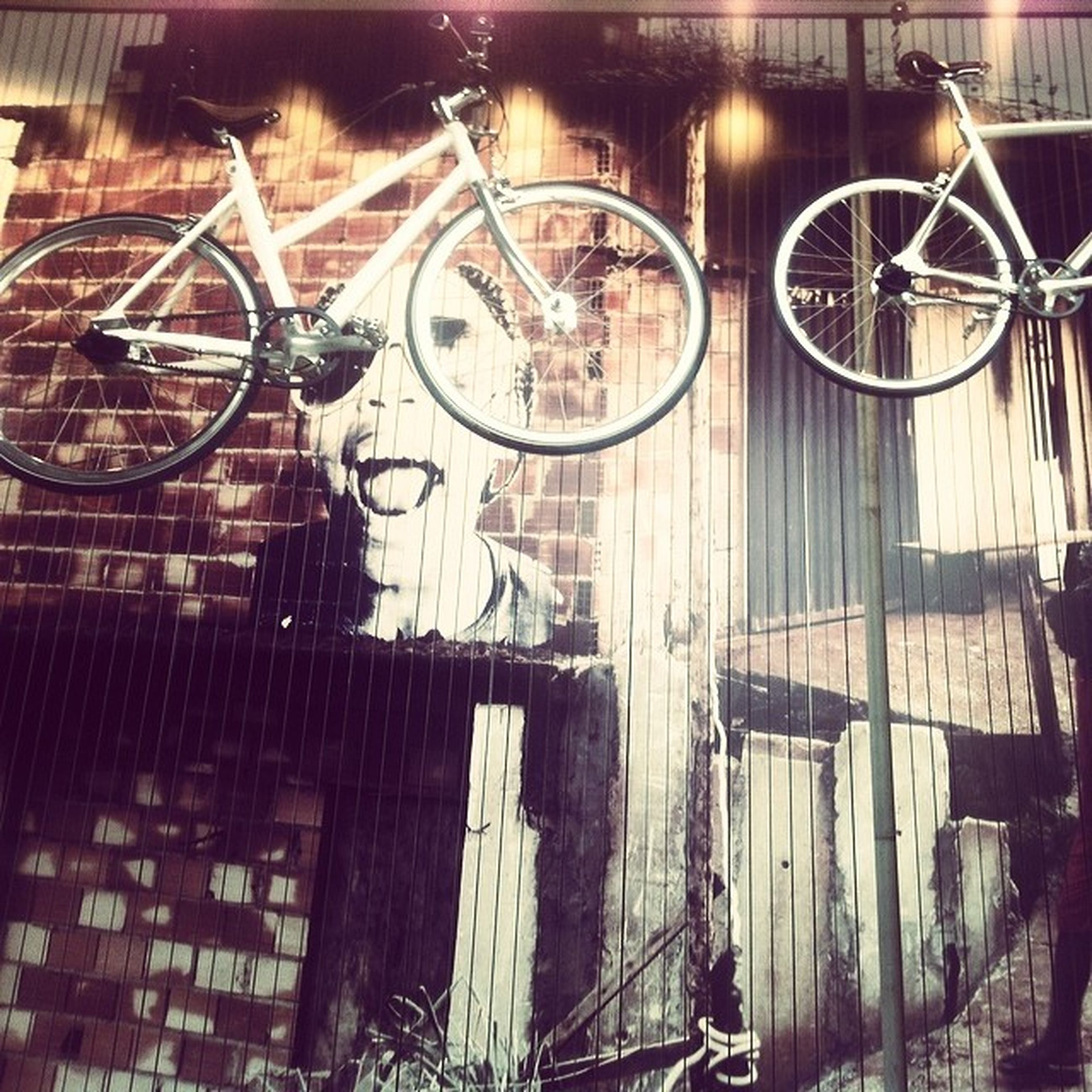 bicycle, transportation, built structure, building exterior, architecture, mode of transport, land vehicle, wheel, stationary, night, parking, metal, outdoors, wall - building feature, art and craft, street, art, no people, city, arts culture and entertainment
