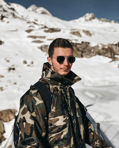 Portrait of man wearing sunglasses standing in snow